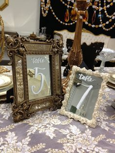 Mirrored frames with calligraphy for wedding table numbers.