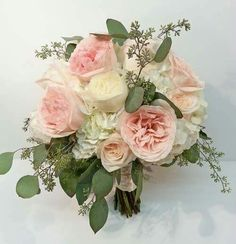 Loose and natural garden roses and hydrangea are accented with trailing seeded…