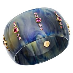 "Mark Davis ""Glenda"" Marbled Blue Gem-Set Bakelite Bangle with circular-cut pink sapphire and rubelite accents mounted in 18k yellow gold settings. Pink sapphires weighing 3.24 total carats and rubelites weighing 4.14 total carats. 2.5"" approximate interior diameter."