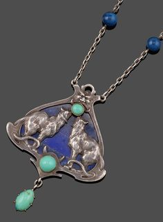 An Art Nouveau silver lapis lazuli and turquoise pendant by Paul Briançon, depicting two well detailed facing large cats, the lapis lazuli background depicting the night sky. The silver frame with grotesque mask above and the lynx style cats tails looping through the shaped lower section. Mounted with three turquoise cabochons. Signed Briançon to each reverse corner. 7.5cm wide. With blue beads mounted to the silver chain.