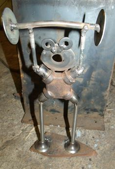 This is a scrap metal art weight lifter by Rusted Iron Studio made from scrap metal auto parts.