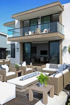 Oceanside home boasts a second floor floating balcony shading a patio filled with wicker sectional and chairs lined with black and white pillows facing a fire pit with ceramic fire balls.