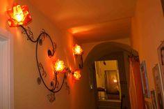 Lampada da parete, ramo di Rose. Questa applique alloggia su tutta la lunghezza, 4 fiori di rosa rossi, che ospitano ognuno 1 portalampada E14.