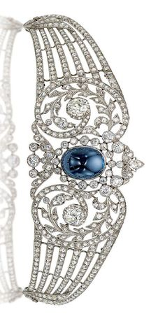 A BELLE ÉPOQUE SAPPHIRE AND DIAMOND TIARA. Centring upon a collet-set cabochon sapphire in a rose and old-cut diamond scrolling frame, extending tapered openwork diamond-set branches, circa 1910