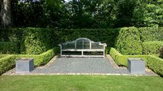 Formal wood bench sits atop a bed of blackstar gravel lined with red brick. Japanese yews and trimmed boxwood hedges frame this classic english seating area.