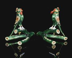 Two gold polychrome-enamelled and gem-set parrots on a branch, North India, 19th/20th century each parrot holding a red and gold lotus, with enamelled green body, red and blue detailing to the wings, each perched on an emerald-coloured twig, gem-set details to eyes, wings and branch, including diamonds Quantity: 2 6.5 by 6.5cm. each