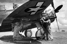 A P-47 named Miss Mary Lou is being armed with M8 Rockets, Saipan, 1944.