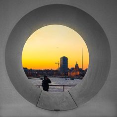 I took a photo of someone photographing the Samuel Becket Bridge through the round window part. The sun was just below the horizon so the city in the background was glowing orange. The little dots are all seagulls or perhaps other types of birds. Dublin at night. Window Parts, How To Take Photos, Take My, Dublin, Bridge, Dots, Windows, Sun, Gray