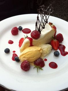 Baked white chocolate cheese cake drizzled with red berry coulis