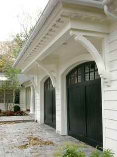 Black garage doors with panes, white house and pergola, talk about curb appeal Black Garage Doors, Black Doors, Black Shutters, White Siding, Painted Garage Doors, Black Windows Exterior, Black Exterior, Wooden Doors, Nachhaltiges Design