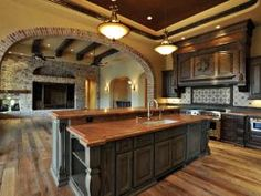 Tuscan kitchen. I want lighter cabinets, but this concept flow into the living room is what we want. Wide open floor plan. Matt Goold