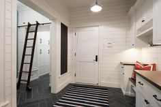 Stylish black and white cottage mudroom features a black and white striped rug placed atop dark gray slate herringbone floor tiles lit by an industrial cage pendant. White Shiplap, Brick Tiles, White Cottage, Striped Rug, Mudroom, Herringbone, Laundry Room, Tile Floor, New Homes