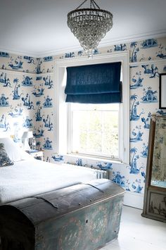 Bedroom covered in blue and white wallpaper