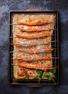 Grilled fried prawns shrimps Langostino Austral on skewers on metal grid baking sheet on black background