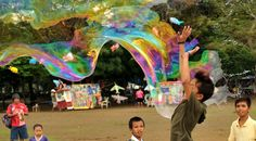 A boy jumps into a huge bubble created by Andrew Ang at Luneta Park in Manila. Ang has created a formula to make huge bubbles and sells the liquid solution at the park.
