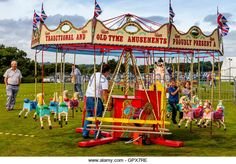 Children Riding On A Traditional Carousel (merry-go-round), The Annual Hartfield Village Fete, Hartfield, East Sussex, - Stock Image