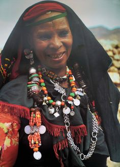 "Africa | ""Women from the Draa Valley in southern Morocco decorate their long plaited hair with rings of silver, agate and glass, and hang bunches of branch coral, shells and old silver coins from the ends. In recent years costly elements of coral and amazonite have been superseded by red and green glass beads, as seen in the woman's necklaces."" 