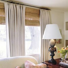 linen drapes w/ woven roman shades.. curtain rod extending wider than windows. Would be great for the family room