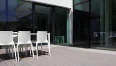 Moderne Wohnfläche. Terrasse und Wohnbereich können im Sommer durch die großen öffenbaren Glasflächen miteinander verschmelzen. Die WPC Terrassendielen im zeitlosen steingrauen Design sind splitterfrei und wetterfest.