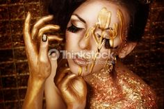 Closeup portrait of beautiful young brunette in gold liquid paint : Stock Photo