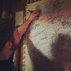 photo by greatbecinthesky: Max signs the Cottage wall.