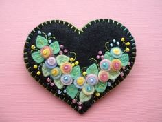 Welcome!    This darling heart pin, made from good quality, wool blend felt, is 2 1\/2 across and 2 1\/4 from top to bottom. Onto black felt, Ive added a spray of colorful little felt flowers, sweet touches of embroidery, and some seed beads. The edges of the heart are neatly blanket stitched. Securely attached to the back is a silver tone pin. This pin is nice and sturdy so you can wear it without it losing its shape, and it should last a long time. Its all very carefully hand sewn. (This…