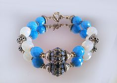 It is a unique bracelet.Charm Bracelet , Blue,White Opaque ,Czech  Crystals.Lovely combination,Czech  Crystals and Metal beads will add a touch of understated bling to any occasion from Winter to Spring Holid  Large beads 12-14 mm.Central bead 14 mm swarovski filigree bead.  Measures 7.5 inches in length.    All jewelry is cleansed and infused with Quantum Healing Energy prior to shipping in a coordinating cloth gift bag..    Please Note:  1) Color refers to that name used by the…