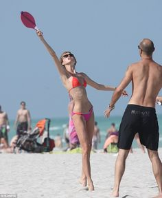 Eye on the ball: The blonde bombshell's prominent ribcage was visible as she played beach ...