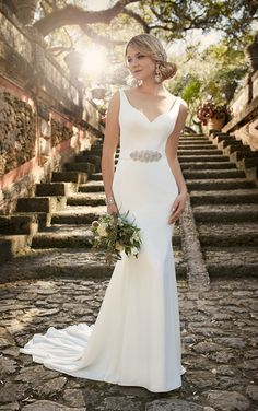 This classic,yet modern, crepe sheath silhouette bridal gown from the Essense of Australia wedding dress collection features a detachable beaded crepe belt, plunging neckline, and a pretty chapel train. It comes in your choice of romantic Ivory and traditional White.