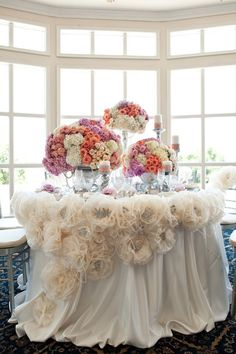 Decor. I love the fluffy tule flowers on the tablecloth and the large colorful centerpieces. It looks expensive, but I bet it could be done as a DIY project. :)
