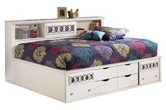 """The Zayley Youth Bookcase Bed from Ashley Furniture HomeStore (AFHS.com). With a bright replicated white paint finish flowing cleanly over the decorative """"Egg and Dart"""" lattice accents, the """"Zayley"""" youth bedroom collection offers an exciting contemporary design that features the versatility of 9 interchangeable color panels to add you own personal flair to the bedroom décor."""