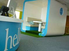 A freestanding meeting pod in an open plan office and a curved reception desk