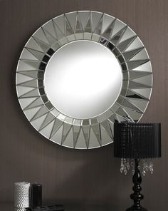 This dramaticaly styled attractive modern round mirror has a broad circular border with a bevelled multi point star pattern which creates interesting subtle multifacet effects. The clear glass bevelling is continued as the inside of the border to where it meets the main part of the mirror. It's unique design makes this item a cool one-off.
