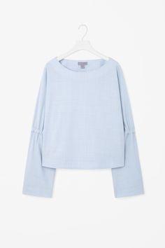 This top is made from a wool-blend with a slight stretch and a subtle melange effect. A loose fit, it has gathered elasticated details on the sleeves, a wide round neckline and neat finishes.