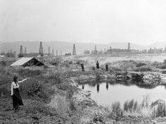 1910 : The small pond at La Brea tar pits, which is now in central Los Angeles, California. Beyond is the Hancock oil field with oil derricks stretching across the land.