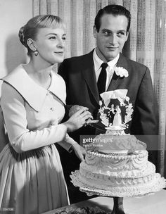 American actors Joanne Woodward, wearing a pale-colored dress with a pleated skirt, and Paul Newman