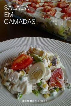 Essa salada é preparada em camadas e leva alface, queijo, peito de frango, ervilha, milho, palmito e uma cobertura de maionese com creme de leite