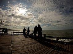 Pesca de Pejerrey con caña en el muelle La Lucila del Mar. Paisaje con siluetas de pescadores a contraluz .