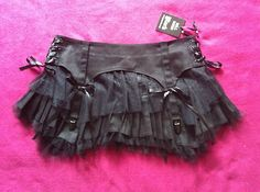 I always see tiny leather skirts and pants at yard sales. they have lots of useful leather and are always cheap. Cut them up the sides. Add some leather from the bottom part to make them fit you and lace em up. Wear over a tutu or anything. This is a great starting point for a utility belt or steampunk garter.