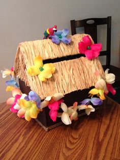 Tiki hut card box made from a cardboard box, painted Popsicle sticks, raffia, and some dollar store leis (and a cute little parrot I found at the dollar store.
