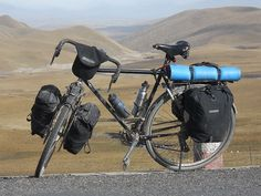Touring bicycle equipped with front and rear racks, fenders/mud-guards, water bottles in cages, four panniers and a handlebar bag.