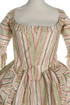 A striped chine taffeta robe à la Française, 1770s. the silk woven in shades of green pink and ivory, the open robe with closed front bodice, linen linings, double engageants, pinked furbelows to the skirt edging, with matching petticoat