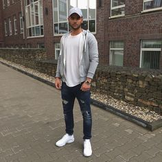 Busy days call for a simple yet stylish outfit, such as a grey hoodie and navy distressed jeans. To break out of the mold a little, make white athletic shoes your footwear choice.   Shop this look on Lookastic: https://lookastic.com/men/looks/hoodie-crew-neck-t-shirt-jeans/21047   — Grey Baseball Cap  — Grey Hoodie  — White Crew-neck T-shirt  — Navy Ripped Jeans  — White Athletic Shoes