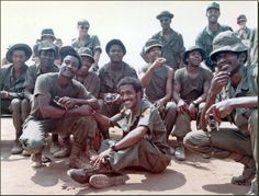 """Sammy Davis, Jr., a United Service Organizations performer and part of President Nixon's anti-drug program, talks with troops at Bien Hoa Air Force Base, Vietnam on February 22, 1972. Davis, a World War II veteran, observed a different military experience in Vietnam: """"They're regarding men as individuals. When I was in the Army, I was on a post where a colored guy couldn't get his hair cut."""" (National Archives)"""