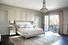 Antique rug and French Empire chandelier custom upholstered bed, mirrored chest.