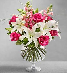 Elegant Elixir™ includes pink roses, white lilies, snapdragons and stylish bear grass in a brandy snifter