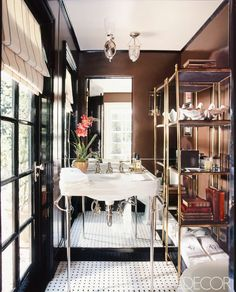 Get Inspired by These Absolutely Elegant Small Bathrooms via @domainehome// In this powder room, a mirrored wall visually doubles the size of the space. A sink balanced on thin chrome legs makes the piece appear as if it's floating.