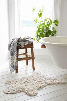 Rustic and elegant wood stool in white bathroom with freestanding tub and faux sheepskin bath rug