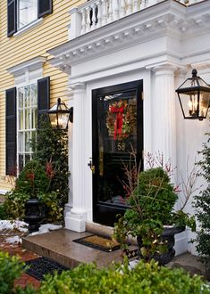 The entry displays classic hallmarks of the Georgian Colonial Revival style. Red berries on delicate branches and a simple decorative bow on the wreath add just the right dose of holiday charm.