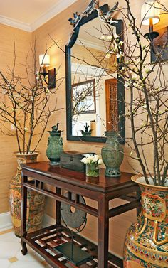 "Powder Room  Quince branches and Asian-inspired vases flank an antique Chinese console from the White Lotus Collection in Melissa Ziober and Noe Guerra's peaceful powder room. To maintain the historical home's integrity, the NXG Studio design team first restored the walls, moldings, and floor. ""The space is traditional while still feeling modern and fresh,"" Ziober says."